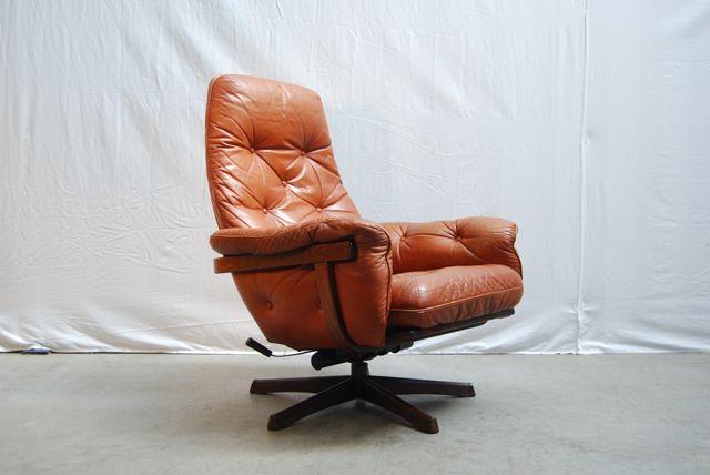 SOLD / Een zeer mooie jaren 70 draaibare fauteuil van Göte Möbel Nassjo / #GMöbel uit Zweden met verstelbare rugleuning. Gebogen houten frame met een cognac kleurige skai leren gecapitonneerde bekleding en armleuningen. De stoel staat op een metalen stervoet welke is voorzien van een houtmotief