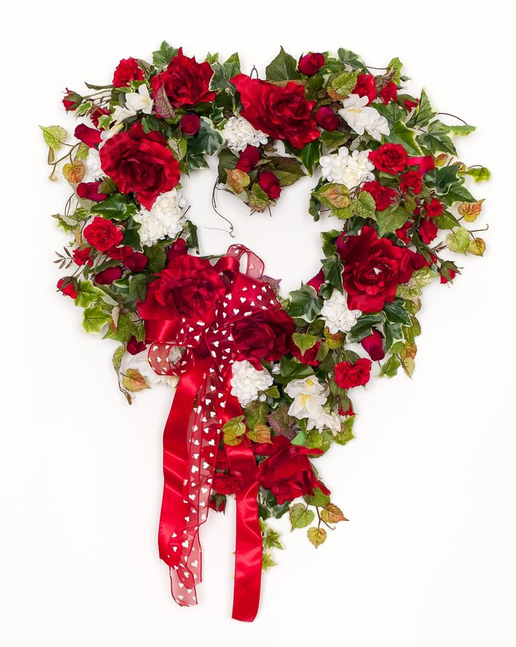 "HW600  $189  28"" Heart Wreath This red rose heart wreath is perfect for Valentine's day, anniversary, or used as an everyday wreath. With red roses in bloom, red rose buds, white hydrangea, this is a classic wreath all set on an all natural grapevine base and framed with a variety of greenery. See more heart wreaths at: http://www.darbycreektrading.com/Heart-Shaped-Wreaths-C156.aspx"