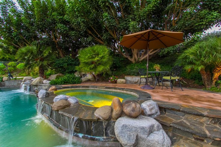 Tropical Hot Tub with Fence, exterior stone floors, Home Loft Concept Sydney Sand Cast Aluminum Outdoor Chair, Raised beds