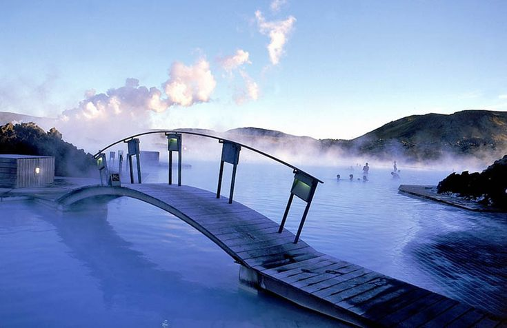 The Blue Lagoon hot springs in Iceland are man-made bodies of water, but the springs are heated naturally with the volcanic activity on the island. The springs are especially beautiful in the snowy winter, and the water still quite toasty.: Buckets Lists, Lagoon Hot, Blue Lagoon Iceland, Beautiful Places, Islands, Bridge, Iceland Travel, Hot Spring, Spa