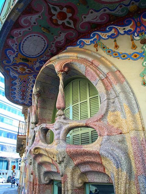 Casa Comalat. La parte de la calle Córcega es totalmente colorista por la decoración a base de cerámica policromada extendida por toda la fachada realizadas por el artista Lluís Bru i Salelles con forma toda ondulante y con galerías de madera cerradas por persianas.