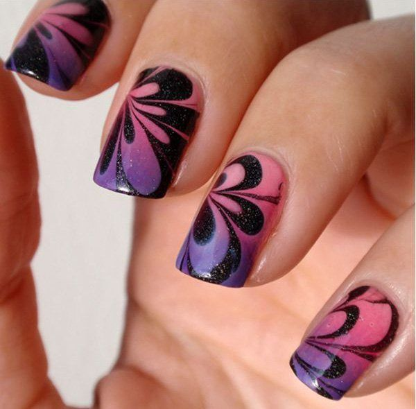 A perfectly flower shaped water marble nail art detail in black, pink and violet colors topped with silver dust sprinkles.
