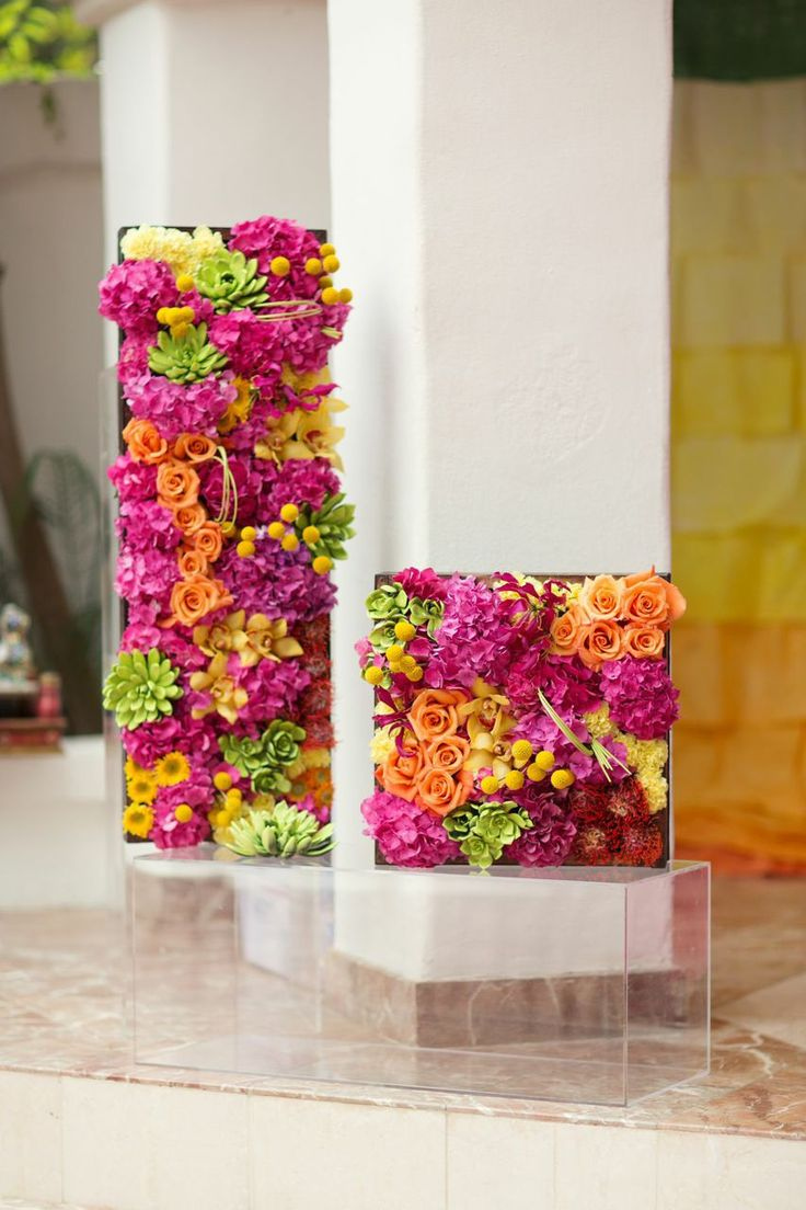 Small flower walls are the perfect wedding decor | See Payal and Stuart's colorful wedding: http://www.xaazablog.com/fun-and-colorful-indian-wedding-lindsay-ricketts-photography/ #floraldecor #flowerdecor #flowerwall #colorfulwedding