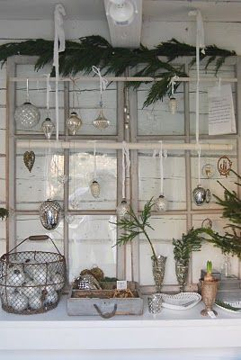 Window frame accented by displaying assorted mercury glass ornaments on wooden dowels : wire basket, wooden tray. lovely.