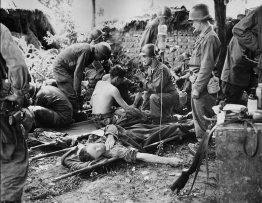 A U.S. Army chaplain prays by injured soldiers at a combat field hospital in Korea
