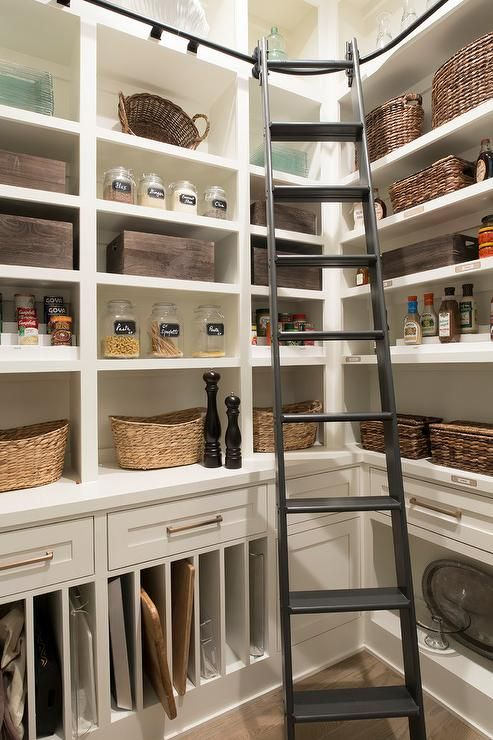 White custom kitchen pantry is fitted with a black ladder fixed to a custom vertical rail lining the top of white cabinets.