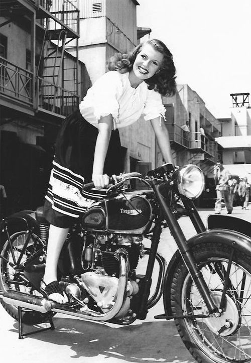 Rita Hayworth photographed with a Triumph motorcycle at Columbia Studios, 1945