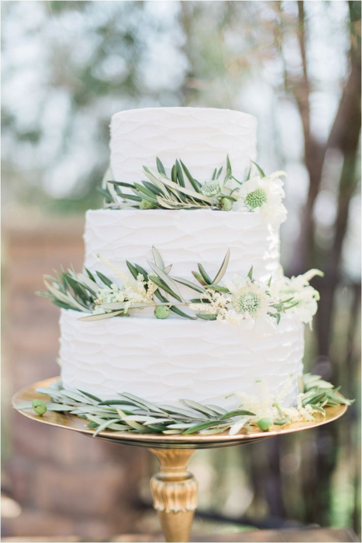 Classic white wedding cake with olive branches and flowers.