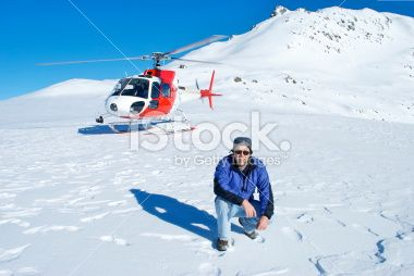 Man and Helicopter on Snowy Mountain Royalty Free Stock Photo