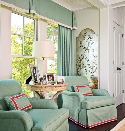 In this sitting area, chairs and curtains sport contrasting trim to counter the matchy-matchy effect. A box-pleat pelmet echoes the skirts on the chairs.