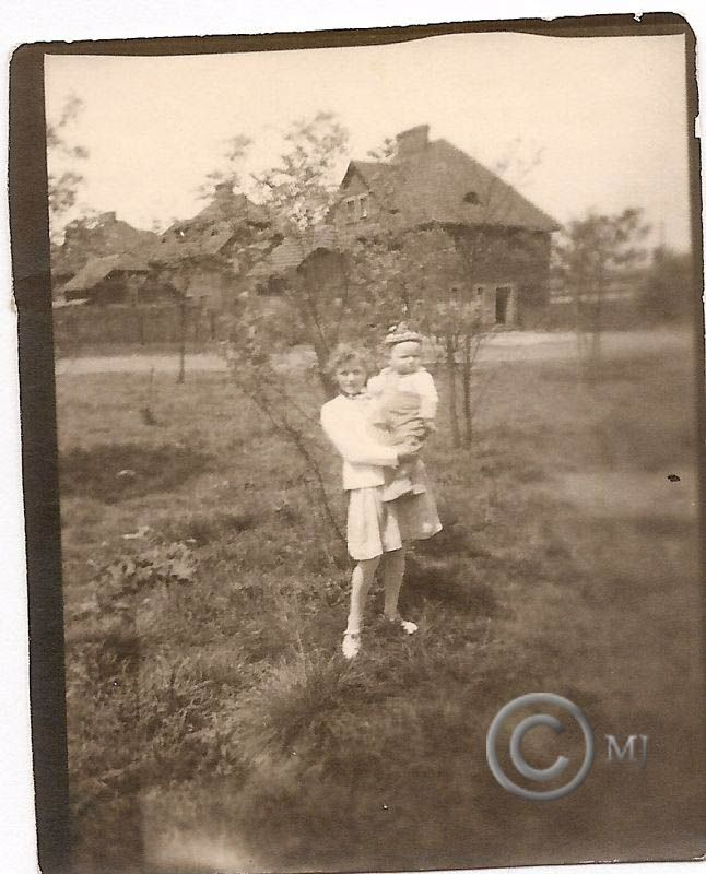 Rodzeństwo pozujące do zdjęcia.W tle budynki przy ulicy StꜶlickiego na Georgshutte.Lata 60 XX wieku.( fot.ze zbiorów Henryka Nikisza)