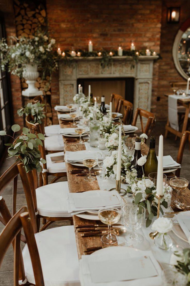 Holzbock-Tische mit weichen grauen Kufen, Taper-Kerzen und weißen Blumen für