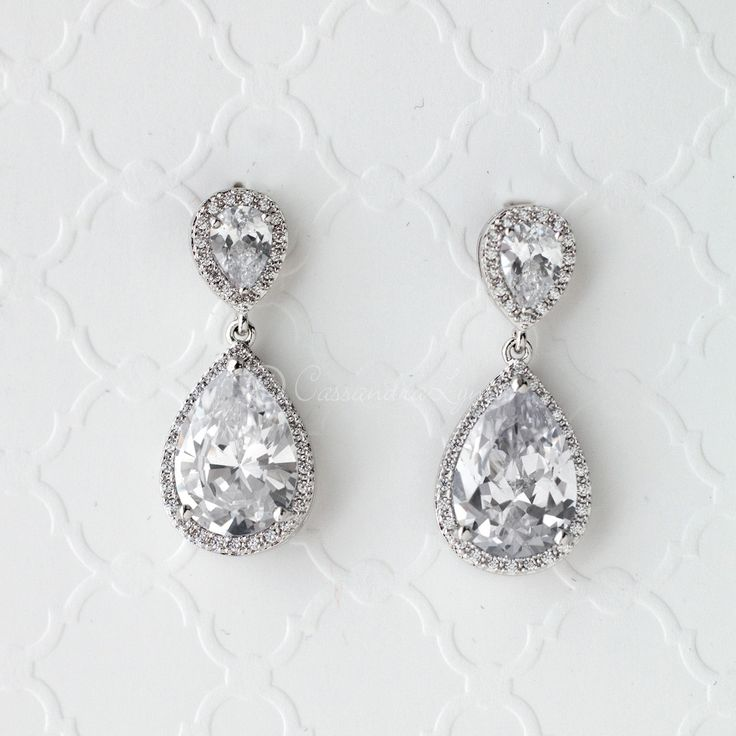 Traditional styled pear drop bridal earrings of radiant CZ jewels. Pierced post backs and 1.25 inches long. Rhodium plated, gold plated or rose gold plated, grade AAA cubic zirconia and lead free.