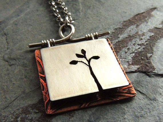 This unique pendant has a 3D effect with the top layer being raised from the bottom layer. The top layer features a nickel silver square cut with