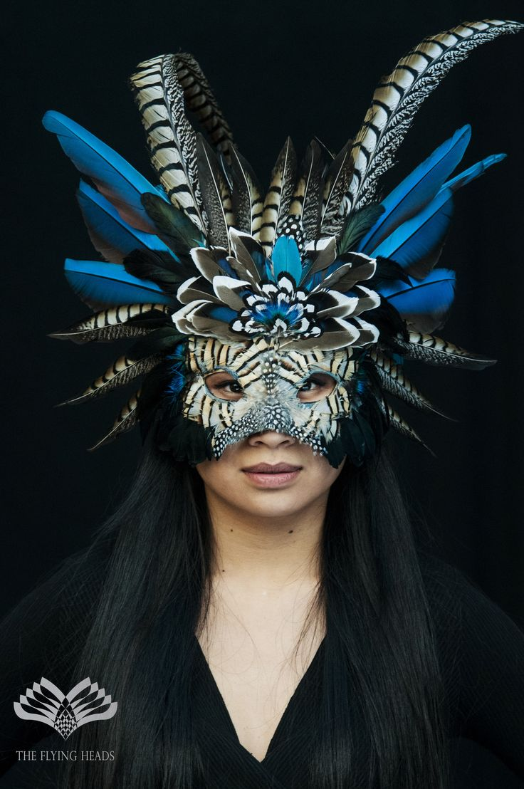**Flying Heads Blue Shamanic Feather Mask ** Wonderfully handcrafted one-of-a-kind tribal feather mask, mainly consists of natural color blue/red ara-parrot and reeves venery pheasant feathers, built up on a recycled carnival mask base surrunded by leather. Perfect for a tribal look on festivals, carnivals, performances, or any occasion where you are brave enough to wear this piece. Guaranteed to have all eyes on you, while still having your face hidden !!