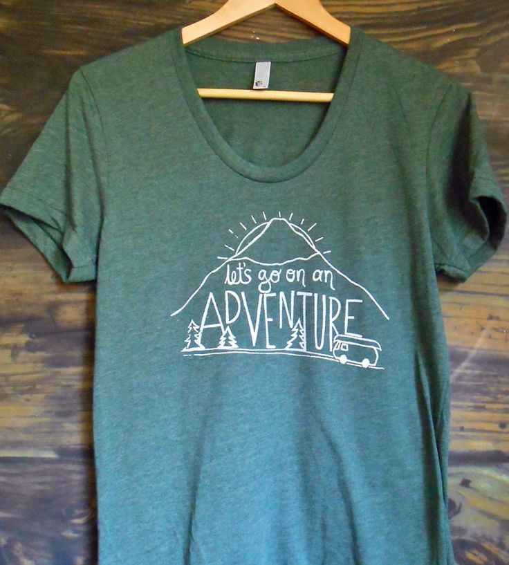 "Prepare for your next adventure with this outdoorsy t-shirt. The hand drawn illustration features a mountain peak, the setting sun, some evergreens, a van and a canoe with ""Let's go on an adventure"" lettered on top. Printed on a soft, breathable tee, it's comfy enough to wear camping, hiking and urban spelunking."