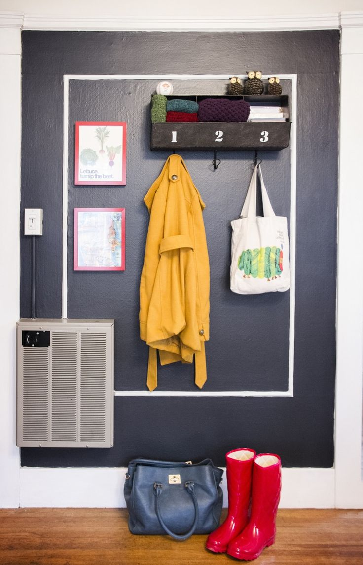 painted wall in organized entryway with hanging jacket boots