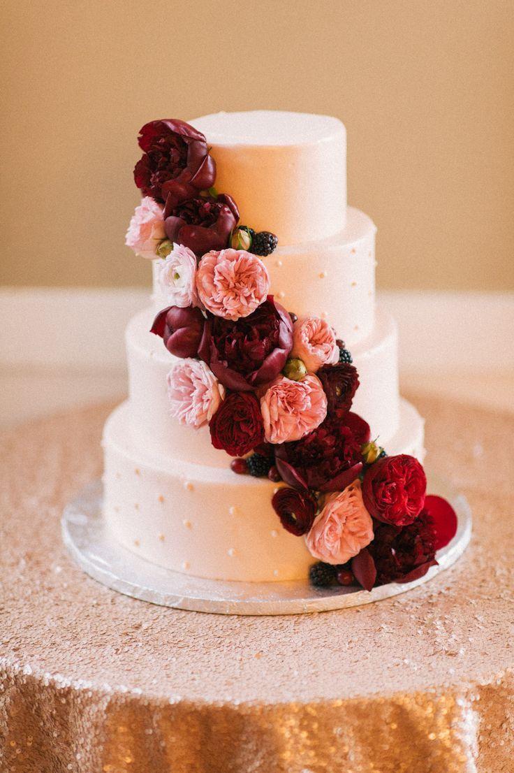 beautiful wedding cake with cascading marsala flowers