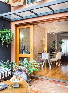Vista da sala de jantar com parede de tijolo e mesa com tampo de vidro.