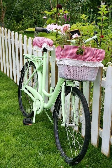 Mint bike with flowers and gingham seat and basket covers with flowers in the basket