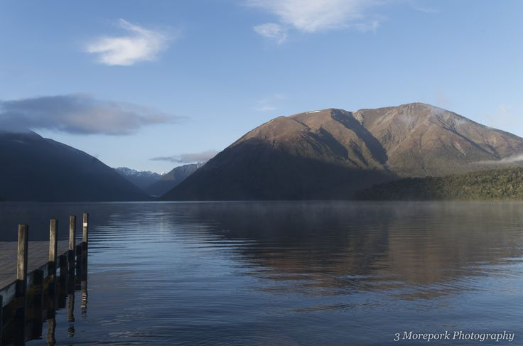 Early morning light catches the mist on Lake Rotoiti, St Arnaud, with Mount Robert in the background. South Island.