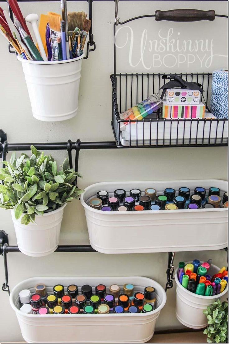Store art supplies in hanging buckets for easy craft room organization.