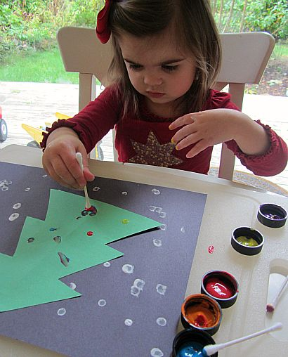 qtip painted Christmas tree craft for toddlers  green paper black paper for background qtips white paint xmasy colors for paint