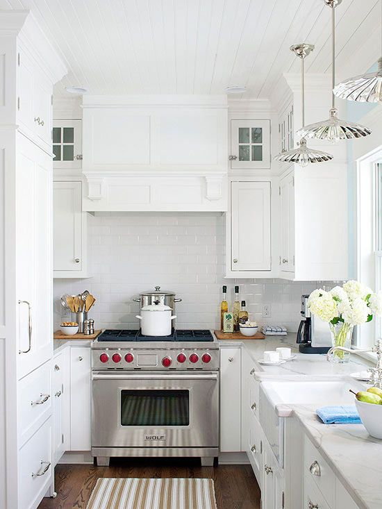 Closing up a doorway transformed a former galley kitchen into a beautiful and efficient kitchen. Custom white cabinetry, classic subway tile, and a beaded-board ceiling create a traditional kitchen with a cottage vibe. The al