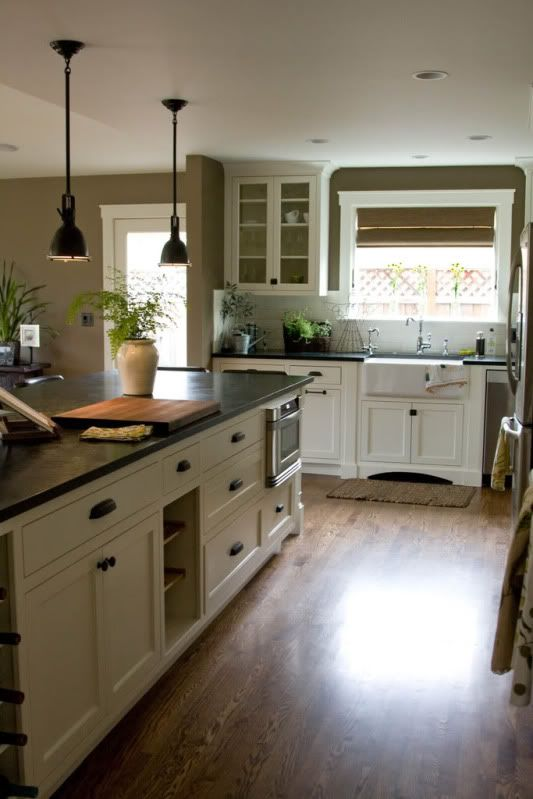 wood floors, white cabinets, dark countertops and hardware and pendant lights