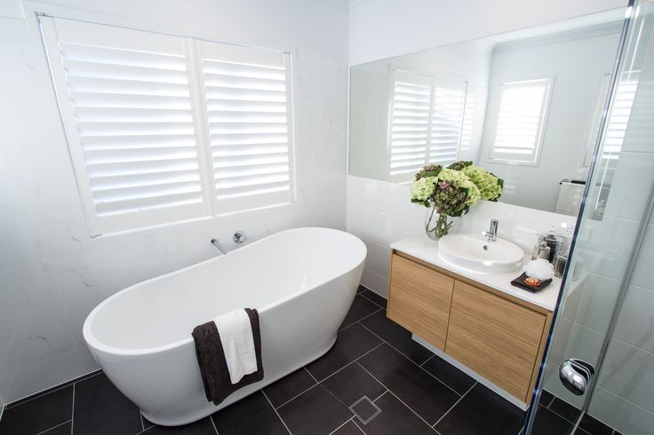 The charcoal floor tiles in the main bathroom have been laid in an interesting herringbone pattern, making the white freestanding bath and vanity pop!