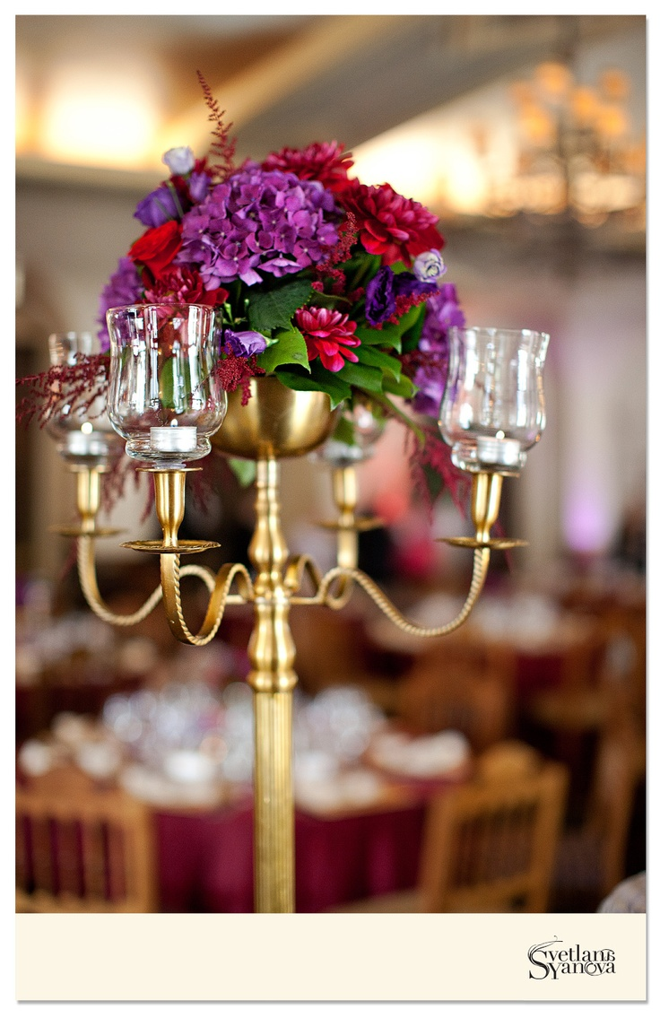 Tall gold candelabras were used in the ceremony as the altar arrangements and then brought back for the reception to flank the head table. Beautiful colors of rich purple and red! (Photo credit: Svetalana Yanova)