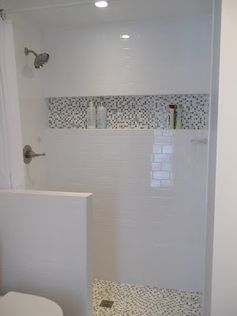 White subway tile shower with full-width shampoo shelf, gray mosaic tile