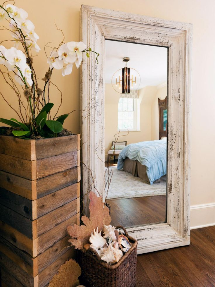 This bedroom design by Vanessa Helmick uses eclectic and coastal decor to provide a rustic feel. The distressed and whitewashed frame on the full-length mirror and planter of reclaimed wood help reinforce the casual and comfortable ambiance. A potted orchid, seashells and coral fans provide accents to complement the theme.