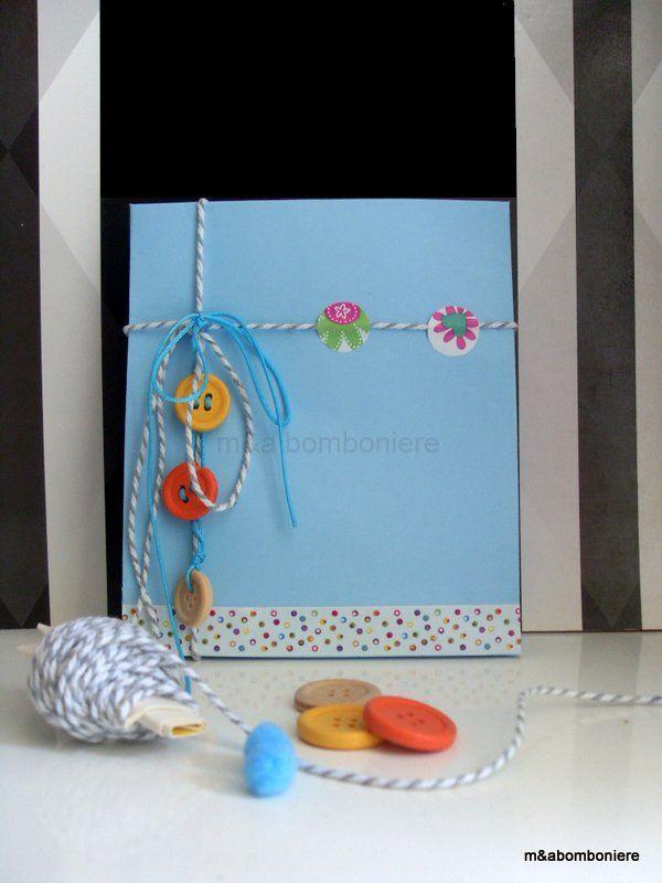 Σε γαλάζιο σακουλάκι, με πολύχρωμα και ξύλινα κουμπάκια, δίχρωμο και τυρκουάζ κορδονάκι και washi tape. Τιμή: 2,00 ευρώ.