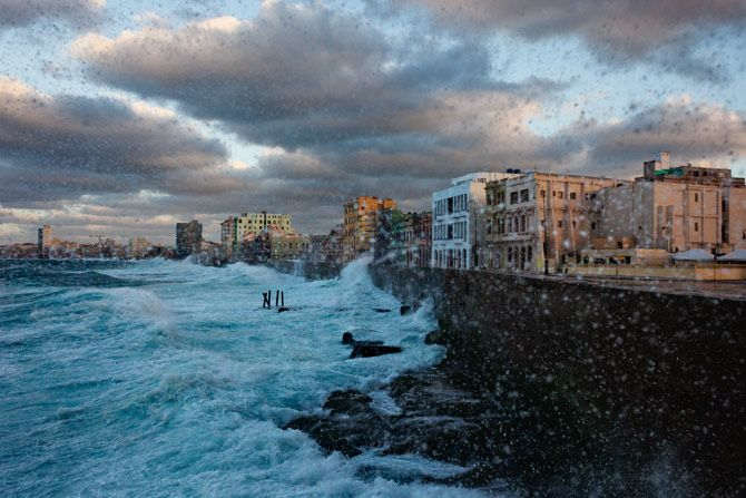 The century-old stone wall of the Malecón, Havana's famous oceanside esplanade, shields the city—imperfectly—from the battering of roiling seas. On calmer nights people come out to stroll on the street.