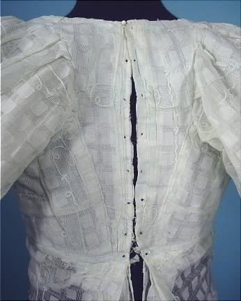 Close up of back closure on white muslin with embroidery. 1800-10