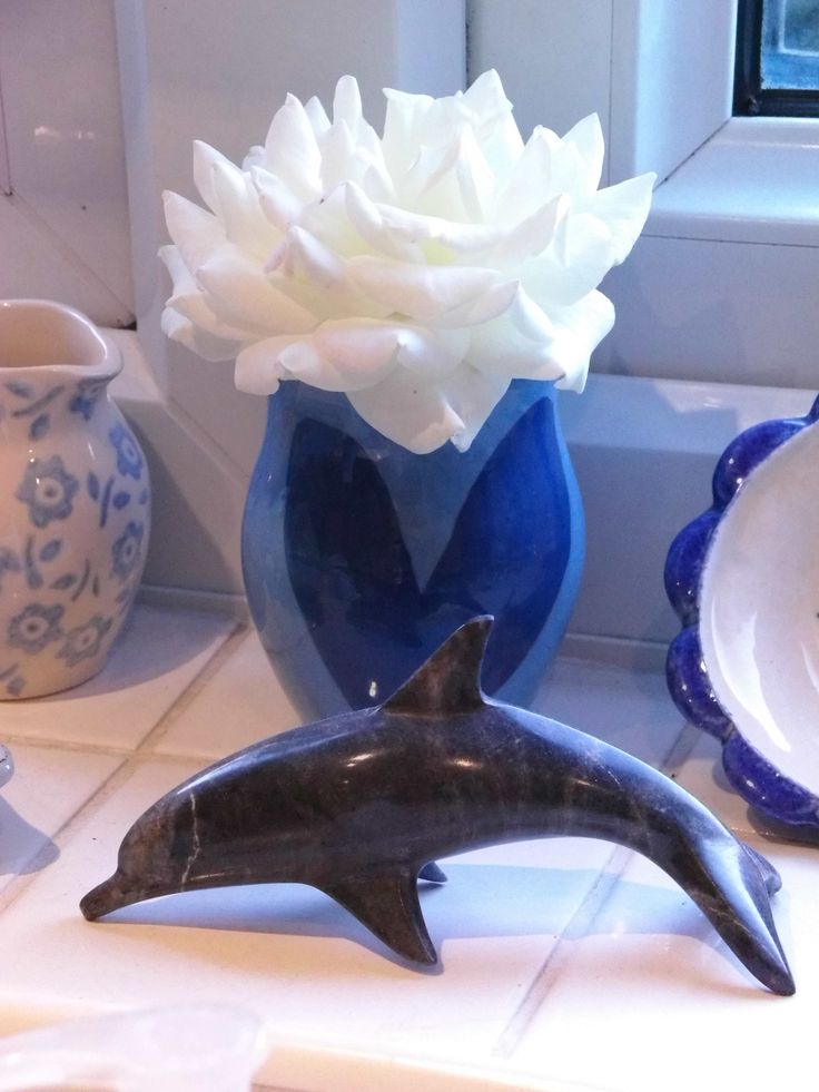 White Rose upon a summer windowsill in a blue pottery vase by a stone dolphin, ceramic jug with blue flower design and a small blue rimmed ceramic saucer.
