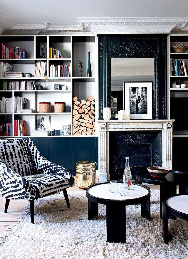 La bibliothèque est faussement blanche : l'intérieur des cases est peint en noir. Le soubassement du meuble, laqué, met en valeur un bleu/noir très profond qui, par contraste avec le reste de la pièce, apporte une touche colorée.