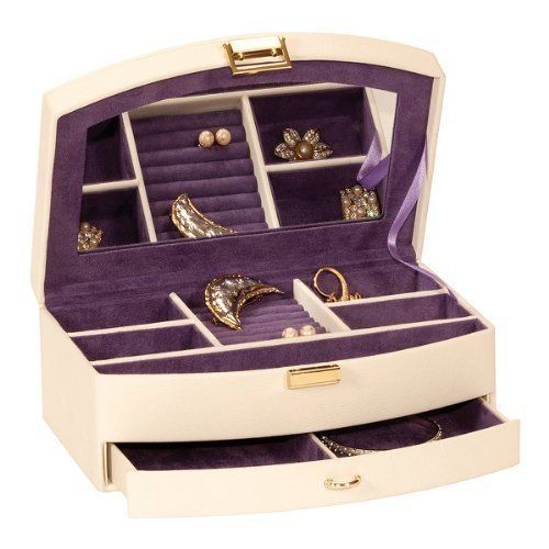 Mele and Co Cream Patricia Jewellery Box Cream jewellery box lined in purple. This box as a mirror integrated into the underside of the lid. The top section has 5 compartments of varying sizes and ring/earring rolls. Underneath is a drawer divided into two for the storage of larger items. 25 cm wide x 16 cm deep x 9.5 cm high approximately.