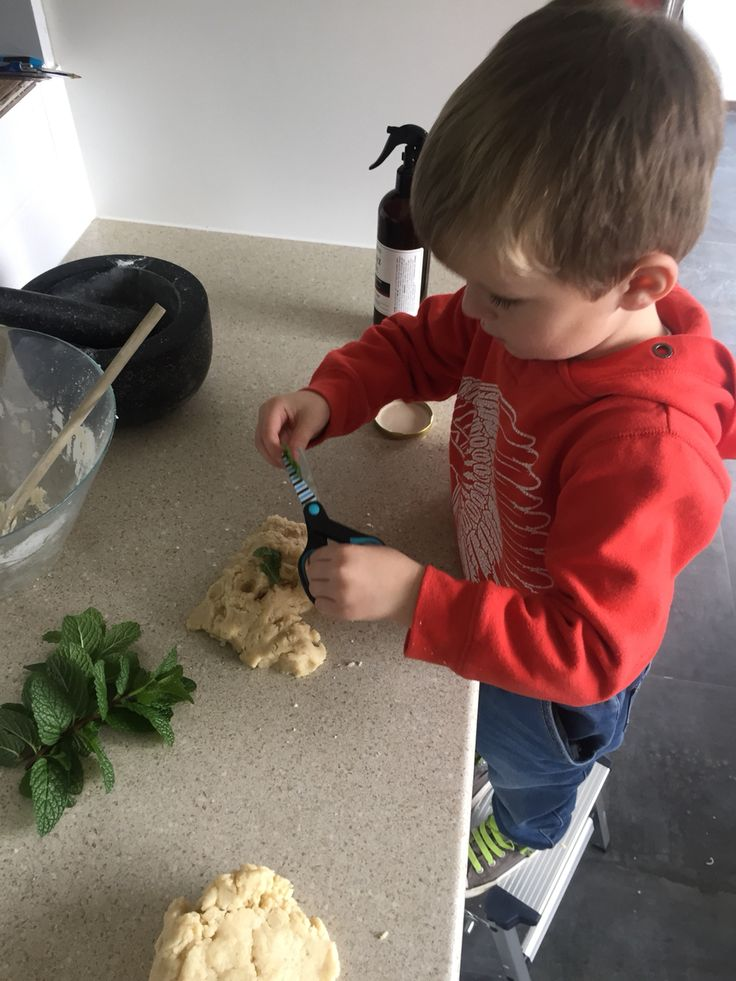 Using scissors to snip mint into play dough