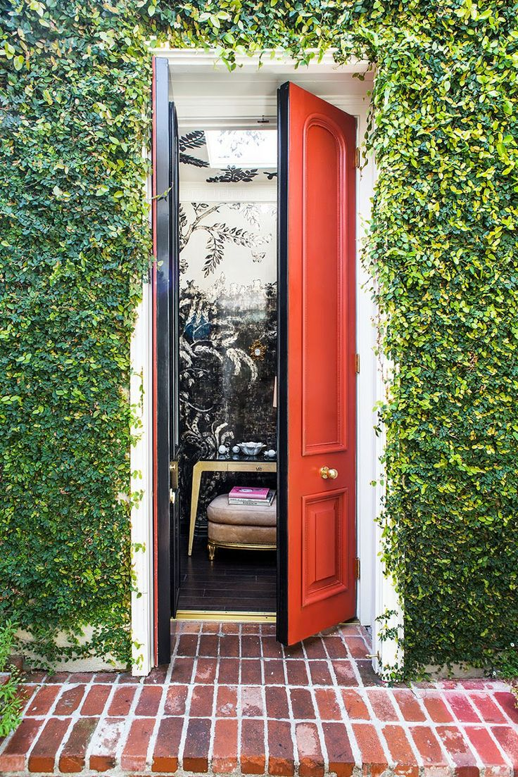 An orange red front door perfectly contrasts against