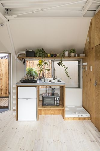 合板で造作したミニマムなキッチン。窓上のスペースを利用して取り付けた棚の下部には、バーを取り付けて使い勝手良く。
