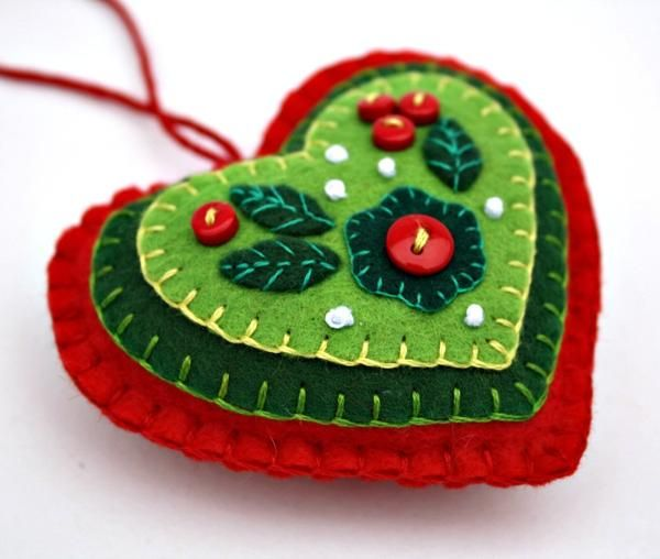 Felt hanging heart with layers of applique and embroidery in red and green, embellished with tiny buttons. A perfect Christmas gift or decoration . 9cm x 8cm approx, with a ribbon loop for hanging.