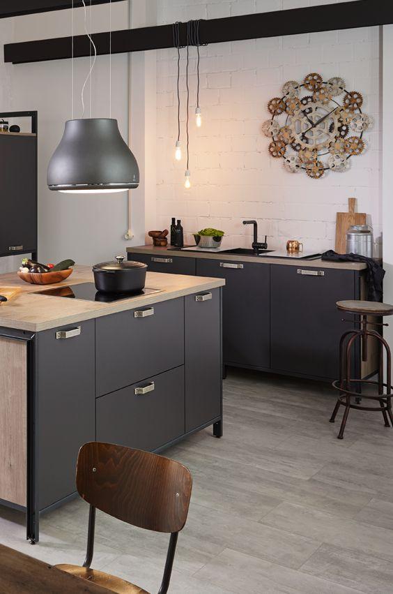 Freistehende Kücheninsel im Industrial Style. Passende Deko wie Metallhocker und frei hängende Glühlampen machen den Look perfekt