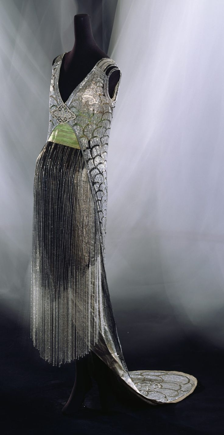 "Evening Dress, Gustave Beer: ca. 1919, silk tulle with bead and rhinestone embroidery, bead fringes, lamé under dress. ""Through the brilliant surface ornaments and straight silhouette of this dress, people could have foreseen the coming 1920s. The scale pattern or 'seigaiha' (blue ocean waves) pattern seen on this dress was used repeatedly in the 1920s as a popular motif of the Art Deco school, whose proponents favored geometric figures..."""