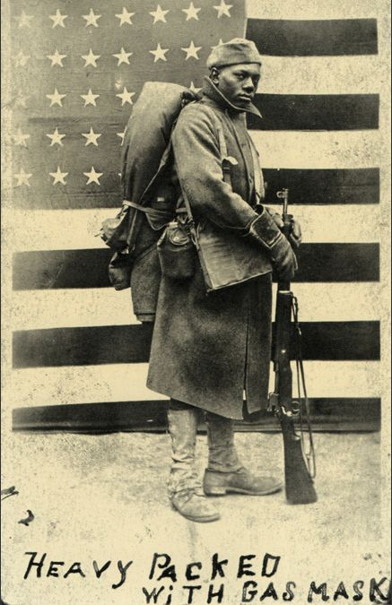 Word War I African American infantryman posing in front of a mockup of the American flag (stars & stripes)