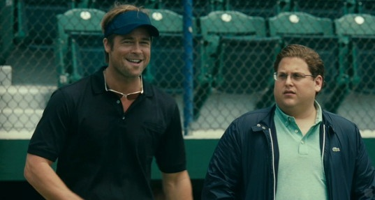 Moneyball Review: Brad Pitt (left) plays Billy Beane, Oakland A's general manager, who tries to put together a baseball team with the help of Peter Brand (Jonah Hill).  History was made when the 2002 Oakland Athletics changed the game of baseball. They did this by opening the door for unwanted players to join their roster. Billy Beane's philosophy was simple: make runs by recruiting players who can get on base, regardless of their other abilities. Beane'. . .