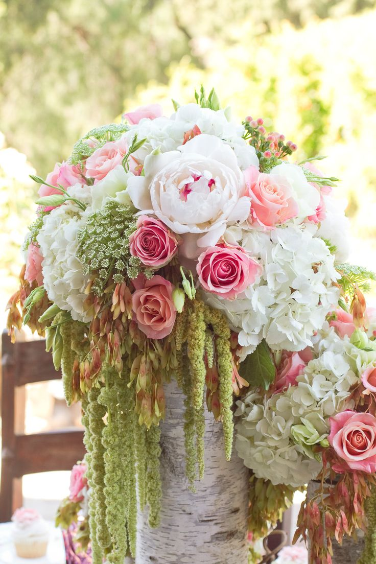 Delicate pink and white flowers with dangling moss and vines in a birch wood vase exude the otherworldly air of a fairy tale