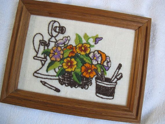 Nicely worked and framed crewel work picture of a pot of orange tone flowers with an antique telephone in the background. Nice compact size that will fit perfectly in a small space - overall size is 8 5/8 by 6 1/2 inches. Excellent condition. No stains or odours.  **Canadian shoppers -