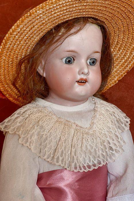 """Een bijzonder fraaie antieke Duitse meisjes pop met porseleinen hoofd gemaakt door Armand Marseille. Ze is gemerkt  """"370 AM . 3  . DEP """".  Ze heeft goed functionerende blauwe slaap ogen. Ze draagt een originele antieke pruik en een stro hoed. Haar lichaam heeft een lederen lijf met pen gewrichten . Haar benen en armen zijn leer, met onderarmen van composiet, waarvan de handjes enig verf verlies hebben. Een blauwe ovaal sticker op haar romp zegt """"Miss Millionaire"""" (zie foto), Königl…"""